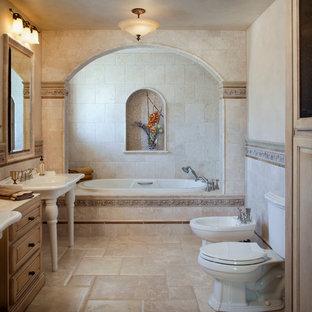 Foto di una stanza da bagno mediterranea con ante con bugna sagomata, ante in legno chiaro, top in marmo, vasca idromassaggio, bidè, piastrelle beige, piastrelle in pietra e lavabo a colonna