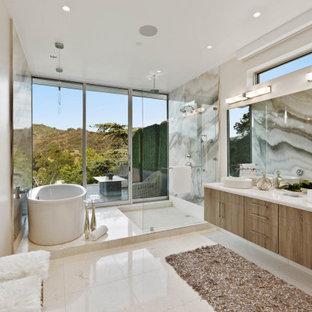 Réalisation d'une grand salle de bain principale design avec un placard à porte plane, une baignoire indépendante, des dalles de pierre, un mur beige, un sol en carrelage de porcelaine, une vasque, un plan de toilette en surface solide, aucune cabine, un plan de toilette blanc, un espace douche bain, un sol beige, des portes de placard en bois brun, un carrelage multicolore, meuble double vasque et meuble-lavabo suspendu.