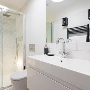 ケントの小さいモダンスタイルのおしゃれなマスターバスルーム (フラットパネル扉のキャビネット、白いキャビネット、バリアフリー、壁掛け式トイレ、白いタイル、磁器タイル、白い壁、磁器タイルの床、壁付け型シンク、珪岩の洗面台、ベージュの床、引戸のシャワー、白い洗面カウンター、洗面台1つ、造り付け洗面台) の写真