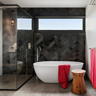 Design ideas for a mid-sized contemporary bathroom in Melbourne with a freestanding tub, a corner shower, black tile, grey walls, grey floor and a hinged shower door.