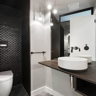 This is an example of a contemporary bathroom in Melbourne with open cabinets, dark wood cabinets, a wall-mount toilet, black tile, mosaic tile, grey walls, a vessel sink, wood benchtops, grey floor and brown benchtops.