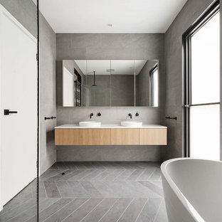 Inspiration for a contemporary bathroom in Melbourne with flat-panel cabinets, light wood cabinets, a freestanding tub, gray tile, grey walls, a vessel sink, grey floor and white benchtops.