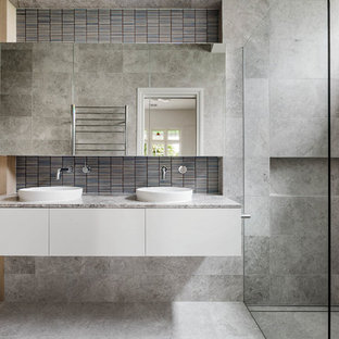 Inspiration for a contemporary bathroom in Melbourne with flat-panel cabinets, white cabinets, a double shower, a wall-mount toilet, gray tile, grey walls, a vessel sink, grey floor, an open shower and grey benchtops.