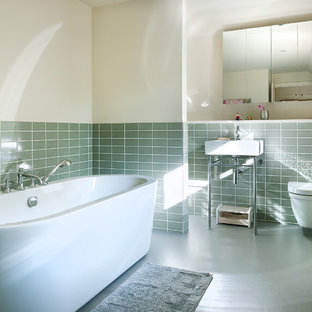 Freestanding bathtub - mid-sized contemporary ceramic tile and green tile linoleum floor freestanding bathtub idea in Hampshire with a wall-mount toilet, white walls and a console sink