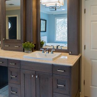 Aménagement d'une salle de bain principale classique de taille moyenne avec un lavabo posé, un placard en trompe-l'oeil, des portes de placard en bois brun, un plan de toilette en granite, une baignoire indépendante, une douche d'angle, un mur bleu et un sol en travertin.