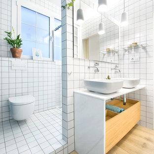 Ispirazione per una stanza da bagno con doccia nordica di medie dimensioni con doccia ad angolo, WC sospeso, piastrelle bianche, piastrelle in ceramica, pareti bianche, pavimento con piastrelle in ceramica, lavabo a bacinella e top in superficie solida
