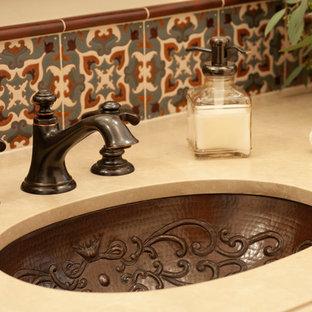 Aménagement d'une salle d'eau méditerranéenne avec des carreaux en terre cuite, un mur blanc et un plan de toilette en calcaire.