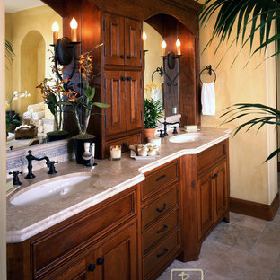 Bathroom - large mediterranean master beige tile and stone tile limestone floor bathroom idea in Santa Barbara with an undermount sink, dark wood cabinets, a two-piece toilet, yellow walls and recessed-panel cabinets