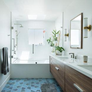 Esempio di una stanza da bagno moderna di medie dimensioni con vasca/doccia, pareti bianche, pavimento con piastrelle in ceramica, lavabo sottopiano, top in quarzo composito, pavimento blu, porta doccia a battente, top bianco, ante lisce, ante in legno bruno e vasca ad alcova