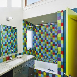 Idée de décoration pour une salle de bain bohème de taille moyenne pour enfant avec un plan de toilette en verre recyclé, des portes de placards vertess, une baignoire en alcôve, un combiné douche/baignoire, un carrelage multicolore, un placard à porte plane, des carreaux de céramique, un mur blanc, béton au sol et un lavabo encastré.