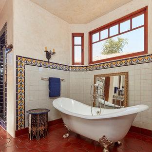 Esempio di una stanza da bagno mediterranea con vasca con piedi a zampa di leone, doccia alcova, piastrelle bianche, pareti beige e pavimento rosso