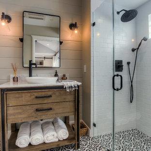 Foto på ett vintage badrum, med möbel-liknande, skåp i mellenmörkt trä, en kantlös dusch, svart och vit kakel, grå väggar, cementgolv, ett fristående handfat, flerfärgat golv och dusch med gångjärnsdörr