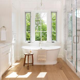 Ispirazione per una stanza da bagno padronale chic con lavabo sottopiano, ante con riquadro incassato, ante bianche, vasca freestanding, doccia alcova, pareti bianche e parquet chiaro