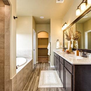 Imagen de cuarto de baño principal, clásico renovado, con armarios estilo shaker, puertas de armario marrones, bañera empotrada, paredes beige, suelo de madera pintada, lavabo bajoencimera, suelo multicolor y encimeras beige