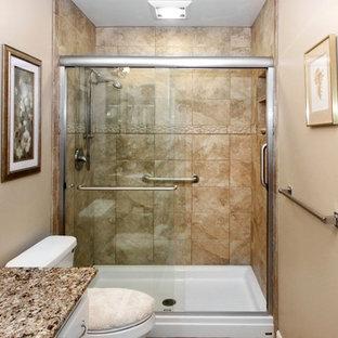 Idéer för att renovera ett mellanstort vintage badrum med dusch, med vita skåp, en dusch i en alkov, en toalettstol med separat cisternkåpa, brun kakel, travertinkakel, beige väggar, ett undermonterad handfat, granitbänkskiva och dusch med skjutdörr