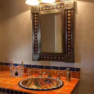 アルバカーキのサンタフェスタイルのおしゃれなバスルーム (浴槽なし) (フラットパネル扉のキャビネット、淡色木目調キャビネット、オレンジのタイル、セラミックタイル、ベージュの壁、タイルの洗面台) の写真