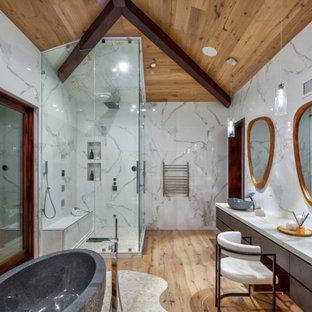 Inspiration för moderna vitt badrum, med släta luckor, skåp i mörkt trä, ett fristående badkar, en hörndusch, vit kakel, mellanmörkt trägolv, ett fristående handfat, brunt golv och dusch med gångjärnsdörr