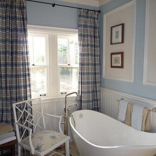 Imagen de cuarto de baño principal, de estilo de casa de campo, de tamaño medio, con armarios tipo mueble, puertas de armario de madera oscura, bañera exenta, baldosas y/o azulejos beige, baldosas y/o azulejos de piedra, paredes azules, suelo de piedra caliza y encimera de mármol
