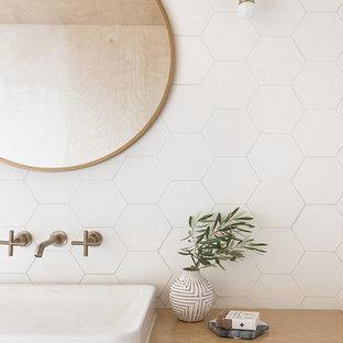 На фото: главная ванная комната среднего размера в скандинавском стиле с плоскими фасадами, светлыми деревянными фасадами, полновстраиваемой ванной, душем над ванной, унитазом-моноблоком, белой плиткой, керамической плиткой, белыми стенами, настольной раковиной, столешницей из дерева, бежевым полом, открытым душем и бежевой столешницей с