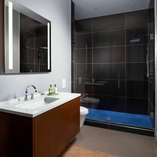 Design ideas for a mid-sized contemporary 3/4 bathroom in Tampa with a one-piece toilet, black tile, white walls, wood-look tile, a drop-in sink, engineered quartz benchtops, brown floor, a hinged shower door, white benchtops, a niche, a single vanity and panelled walls.