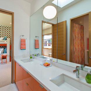サンフランシスコの中サイズのコンテンポラリースタイルのおしゃれな子供用バスルーム (アンダーカウンター洗面器、フラットパネル扉のキャビネット、オレンジのキャビネット、珪岩の洗面台、白い壁、磁器タイルの床) の写真