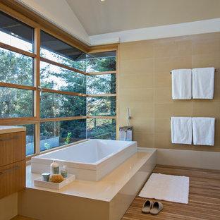 Ejemplo de cuarto de baño principal, contemporáneo, grande, con armarios con paneles lisos, puertas de armario de madera oscura, bañera encastrada, ducha a ras de suelo, baldosas y/o azulejos beige, paredes beige y suelo de madera en tonos medios