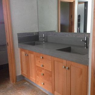 Modelo de cuarto de baño principal, ecléctico, de tamaño medio, con armarios estilo shaker, puertas de armario de madera oscura, baldosas y/o azulejos azules, suelo de cemento, lavabo integrado y encimera de esteatita