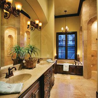 Foto di una grande stanza da bagno padronale mediterranea con lavabo integrato, ante con bugna sagomata, ante in legno bruno, vasca da incasso, doccia ad angolo, piastrelle beige, piastrelle in pietra, pareti beige e pavimento in travertino