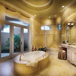 Design ideas for a large mediterranean ensuite bathroom in Miami with a submerged sink, raised-panel cabinets, white cabinets, marble worktops, a built-in bath, a corner shower, a two-piece toilet, beige tiles, stone tiles, beige walls and travertine flooring.