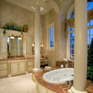 Mediterranean bathroom in Miami with raised-panel cabinets, beige cabinets, a built-in bath and beige floors.