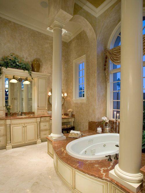 Mediterranean beige floor drop-in bathtub idea in Miami with raised-panel  cabinets and