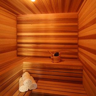 サクラメントの大きいコンテンポラリースタイルのおしゃれなマスターバスルーム (レイズドパネル扉のキャビネット、濃色木目調キャビネット、ドロップイン型浴槽、コーナー設置型シャワー、ベージュのタイル、大理石タイル、ベージュの壁、大理石の床、ベッセル式洗面器、御影石の洗面台、グレーの床、開き戸のシャワー) の写真