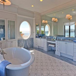 サンフランシスコの大きいビーチスタイルのおしゃれなマスターバスルーム (落し込みパネル扉のキャビネット、白いキャビネット、置き型浴槽、青いタイル、石スラブタイル、グレーの壁、アンダーカウンター洗面器、青い床、モザイクタイル、珪岩の洗面台、青い洗面カウンター) の写真