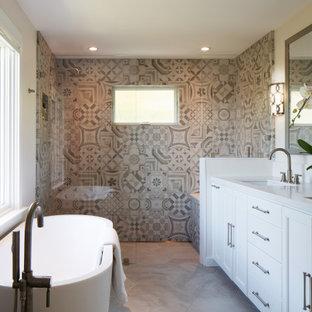 Foto på ett stort vintage vit en-suite badrum, med vita skåp, ett fristående badkar, en dusch i en alkov, beige kakel, keramikplattor, vita väggar, kalkstensgolv, ett undermonterad handfat, bänkskiva i kvarts, beiget golv, luckor med infälld panel och med dusch som är öppen