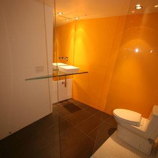 Modelo de cuarto de baño minimalista, grande, con lavabo con pedestal, armarios abiertos, encimera de vidrio, ducha esquinera, sanitario de una pieza, baldosas y/o azulejos grises, baldosas y/o azulejos de piedra, parades naranjas y suelo de pizarra