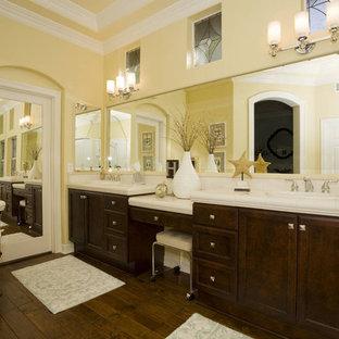 Modelo de cuarto de baño clásico renovado con lavabo encastrado, armarios con paneles con relieve, puertas de armario de madera en tonos medios, encimera de azulejos, baldosas y/o azulejos blancos, paredes amarillas y encimeras blancas