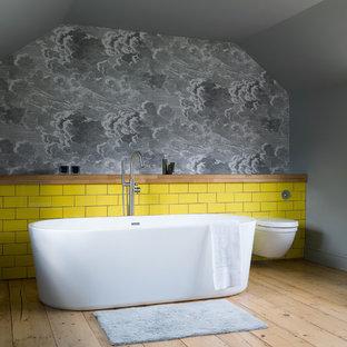 Salle de bain avec un carrelage jaune et un sol en bois clair ...