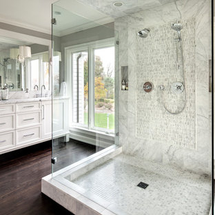 Design ideas for a traditional ensuite bathroom in Milwaukee with recessed-panel cabinets, white cabinets, a double shower, grey walls, dark hardwood flooring and white tiles.
