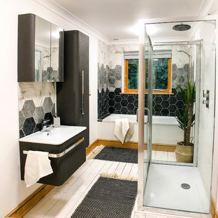 This is an example of a large scandinavian family bathroom in Berkshire with glass-front cabinets, grey cabinets, a built-in bath, a walk-in shower, a one-piece toilet, grey tiles, ceramic tiles, white walls, painted wood flooring, an integrated sink, white floors and a sliding door.