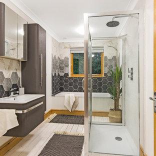 Immagine di una grande stanza da bagno per bambini nordica con ante di vetro, ante grigie, vasca da incasso, vasca/doccia, WC monopezzo, piastrelle grigie, piastrelle in ceramica, pareti bianche, pavimento in legno verniciato, lavabo integrato, pavimento bianco e porta doccia scorrevole