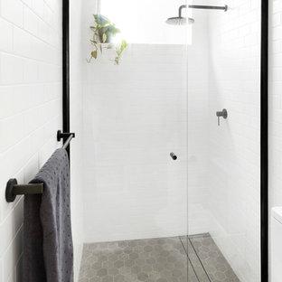Ispirazione per una piccola stanza da bagno scandinava con ante a persiana, ante bianche, doccia a filo pavimento, piastrelle bianche, piastrelle diamantate, pavimento con piastrelle in ceramica, top in laminato, pavimento grigio e porta doccia a battente