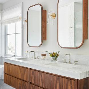 Inredning av ett minimalistiskt vit vitt badrum, med släta luckor, skåp i mellenmörkt trä, vita väggar, ett undermonterad handfat och grått golv