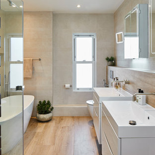 Design ideas for a scandi bathroom in Surrey with white cabinets, a freestanding bath, a one-piece toilet, beige tiles, ceramic tiles, beige walls, ceramic flooring, a wall-mounted sink, solid surface worktops, brown floors, a hinged door and white worktops.