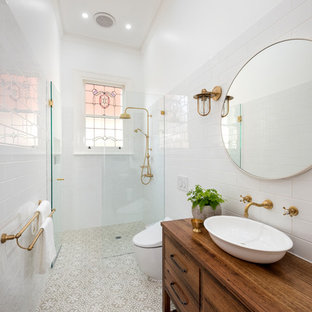 Inspiration for a scandinavian bathroom in Melbourne with furniture-like cabinets, medium wood cabinets, a curbless shower, a one-piece toilet, white tile, white walls, a vessel sink, wood benchtops, beige floor, an open shower and brown benchtops.