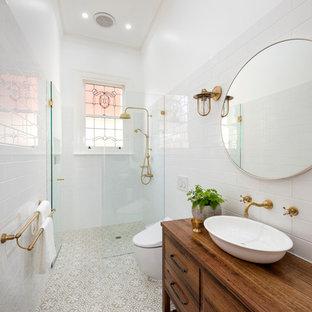 Immagine di una stanza da bagno nordica con consolle stile comò, ante in legno scuro, doccia a filo pavimento, WC monopezzo, piastrelle bianche, pareti bianche, lavabo a bacinella, top in legno, pavimento beige, doccia aperta e top marrone