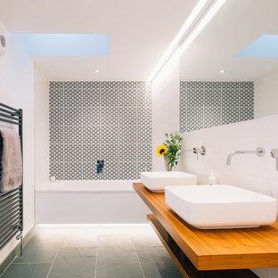 Imagen de cuarto de baño escandinavo, de tamaño medio, con armarios abiertos, puertas de armario de madera clara, bañera encastrada, baldosas y/o azulejos blancas y negros, baldosas y/o azulejos blancos, paredes blancas, suelo de cemento, encimera de madera y encimeras marrones