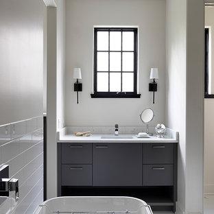 Foto de cuarto de baño escandinavo con armarios con paneles lisos, puertas de armario grises, bañera exenta, baldosas y/o azulejos blancos, baldosas y/o azulejos de cemento, paredes grises, suelo con mosaicos de baldosas, lavabo bajoencimera, suelo blanco y encimeras blancas