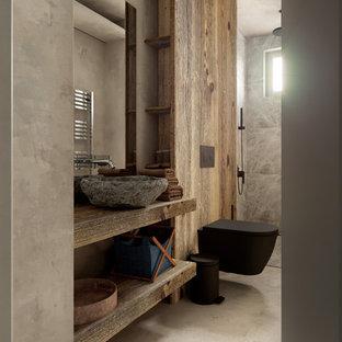 Ispirazione per una piccola stanza da bagno nordica con nessun'anta, ante in legno scuro, vasca ad alcova, doccia a filo pavimento, WC sospeso, piastrelle beige, piastrelle in pietra, pareti multicolore, pavimento in cemento, lavabo a consolle, top in legno e top marrone
