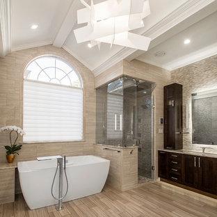 Идея дизайна: большая главная ванная комната в стиле современная классика с фасадами в стиле шейкер, темными деревянными фасадами, отдельно стоящей ванной, угловым душем, бежевой плиткой, керамогранитной плиткой, бежевыми стенами, полом из керамогранита, врезной раковиной и столешницей из оникса