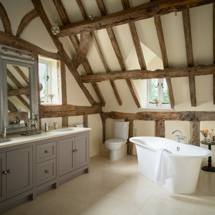 Inspiration for a medium sized rustic bathroom in Cheshire with recessed-panel cabinets, grey cabinets, a freestanding bath, a two-piece toilet, beige walls, a submerged sink, white floors and white worktops.